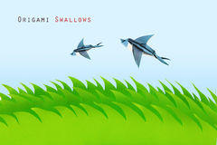 Green field with origami swallows Royalty Free Stock Images
