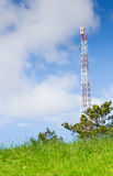 Green field and radio tower Stock Photography