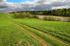Green field and road to anywhere Royalty Free Stock Images