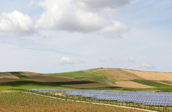 Green field with solar panels. An overall view of some hills and vineyards with a field of solar panels, under a bright cloudy sky, landscape cut Stock Photo