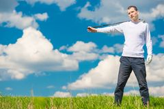 In the green field a successful golfer posing with a golf club o. N a sunny day royalty free stock image