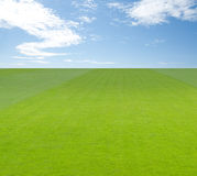 Green field under blue sky with clouds stock images