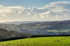 A green field with a village beyond and gowing cumulous clouds ont eh horizon. Cumbria, northern England Stock Photo