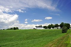 Green field and white barn Stock Images