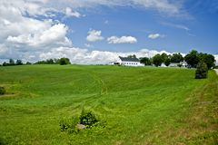 Green field and white barn Royalty Free Stock Photography
