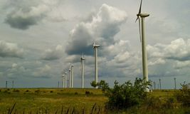 Green field with wind generators. Green field with white wind generators wind turbines in a row, representing sustainable renewable energy Stock Photography