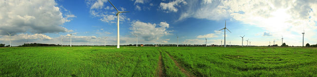 Green field with wind power stations, clouds, blue sky Stock Images