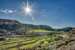 Free Green Field With Hills And A Bright Shining Sun In The Sky Stock Photography - 174558382