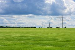 Green field of young wheat, forest, towers of high voltage electrical wires into the distance and the cloudy dramatic Stock Photo