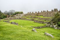 Green fields of ancient Inca Citadel under heavy fog. In Machu Picchu, Peru royalty free stock images