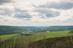 View of Peace River valley from the Peace River Lookout near Fort St. John. Green fields with cloudy sky and view of Peace River and hills in the distance stock photo