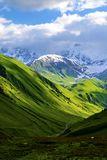 Green fields and hills leading to snow-covered mountains. White clouds are visible behind the lighted mountain top. Summer in Caucasian Georgia. Vertical Stock Photo