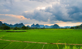 Cloudy field. Green fields with karst hills are covered with cloudy clouds Stock Image