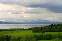 Green fields, lake and snowy mountains Stock Image