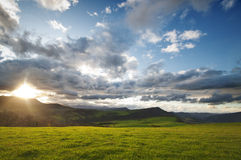 Green fields and mountains at sunset Stock Images