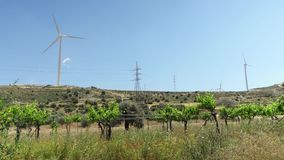 Fields with windmills in Larnaca, Cyprus. Renewable energy resource of alternative energy production. Green fields with power lines and windmills in Larnaca stock video footage