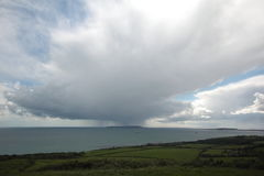 Green fields and rain cloud. Huge rain cloud over Portland, Dorset, uk Royalty Free Stock Images