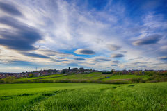 Green fields and small village in early spring. Cloudy blue sky Stock Photography