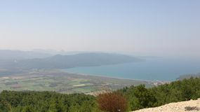 Green fields top view. View from mountain road on green fields and sea with mountain and sky on background in Turkey Royalty Free Stock Image