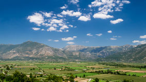 Green Fields Under Mountains. In Greece Stock Image