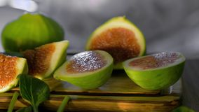 Green figs and basil. Close-up shot of basil leaves falling on cut green figs on wooden board stock video footage