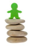 Green figurine on a stack of pebbles royalty free stock images