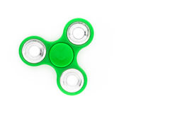 Green finger spinner. Stress anxiety relief toy isolated on white background. Overhead view royalty free stock photo