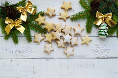 Green fir branches and decoration with gold bows and star-shaped cookies on a white background. Christmas theme Stock Images