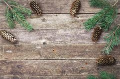 Green fir and pine branches with cones on a wooden gray texture. Christmas and New Year background. Space for text. stock photography