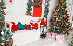 Green fir-tree with red and gold Christmas toys with sofa Royalty Free Stock Image
