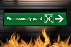 Green fire assembly point sign hanging from ceiling with fire. Flames are burning on the ground below. security based quality awareness concept Stock Images