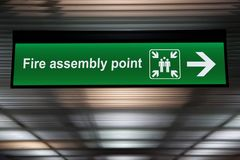 Green fire assembly point sign hanging from ceiling Royalty Free Stock Photos