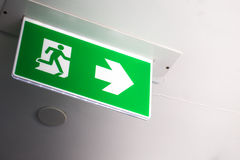 Green fire exit sign in the building. Royalty Free Stock Image