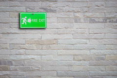 Green fire exit sign on stone wall. Background Royalty Free Stock Image