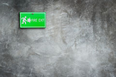 Green fire exit sign on stone wall. Background Royalty Free Stock Photo