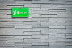 Green fire exit sign on stone wall. Background Stock Image