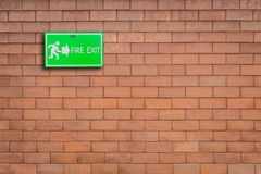Green fire exit sign on stone wall. Background Royalty Free Stock Photography