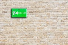Green fire exit sign on stone wall. Background Stock Photos