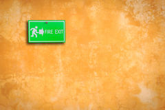 Green fire exit sign on stone wall Stock Photos