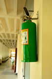 Green fire extinguisher on wall. In a office environment Royalty Free Stock Images