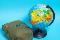 Green first-aid kit next to the globe on a blue background royalty free stock photo