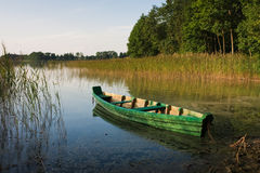 Green fishing boat. Green wooden boat tied up at the shore of a calm lake Stock Images