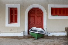 Free Green Fishing Boat In Front Of A Red Door In Agios Nikolaos In Crete Greece. Stock Image - 135274851