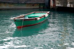 Green fishing boat. A small vessel propelled on water by oars, sails, or an engine Stock Photo
