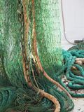 Green fishing trawl net in a trawler boat. Green fishing trawl net henging on a trawler boat deck royalty free stock images