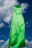 Green flag. A green flag on the wind over a blue sky Stock Photography