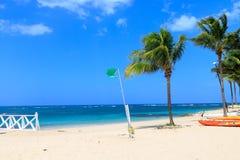 Green flag on the beach indicates no danger when bathing. Dominican Republic royalty free stock photos