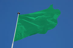 Green Flag. Flying in a stiff breeze against a clear blue sky Royalty Free Stock Images