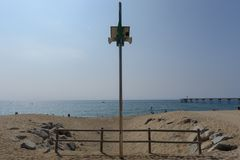 Green flag on the pole. The green flag qualification for the beach on a metal pole with a bridge at the bottom at Badalona, Spain Stock Photography