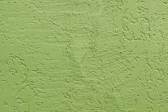 Green flat rough painted cement wall with many cavities. Seamless texture. Used as a background. stock photography